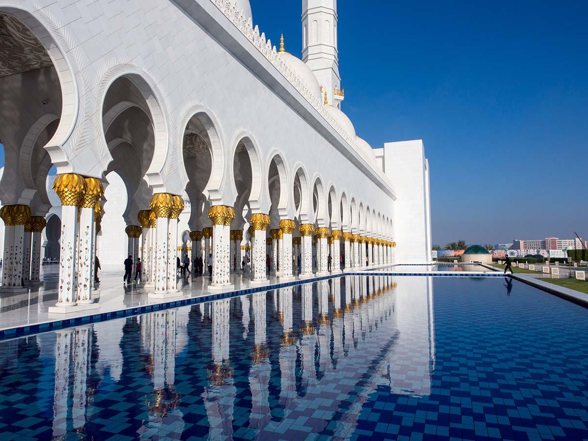 Vergoldete Marmorsäulen spiegeln sich im Wasser vor der Moschee